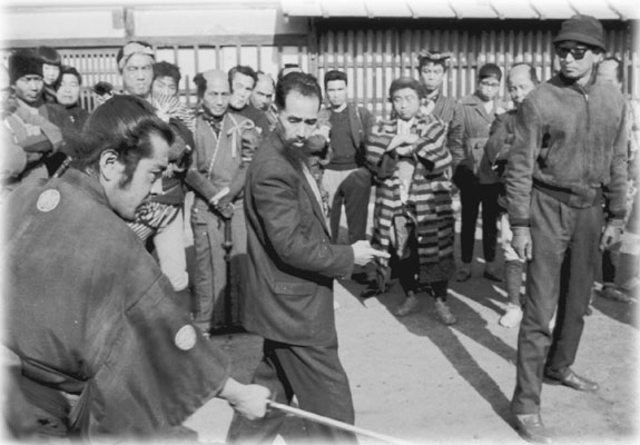 "Yoshio Sugino instructs Toshiro Mifune on the set of ""Yojimbo"" while Director Akira Kurosawa looks on"