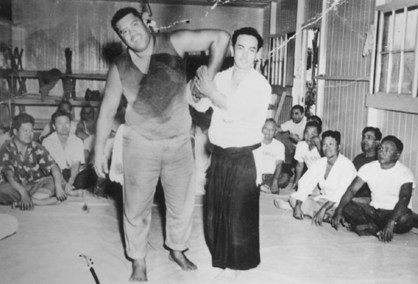Koichi Tohei applying sankyo on huge Hawaiian, c. 1953