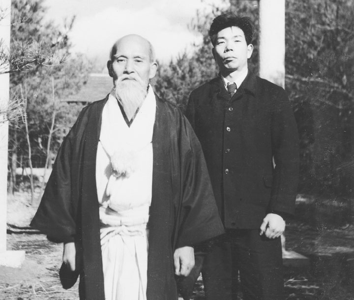 Aikido Founder Morihei Ueshiba with Morihiro Saito in front of the old Aiki Shrine c. 1955