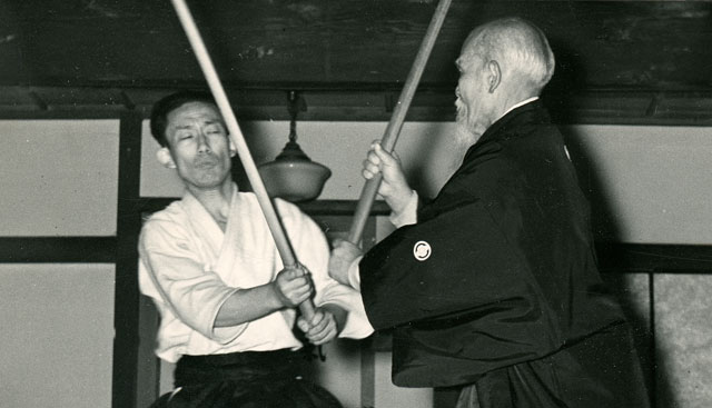 O-Sensei demonstrating sword kata with son Kisshomaru Ueshiba in Iwama Dojo, c. 1957. Courtesy of Andre Nocquet
